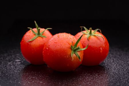 Three ripe tomatoes on a dark background.