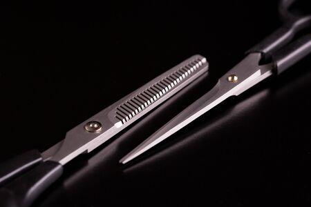 Scissors hairdresser close-up on a black background.