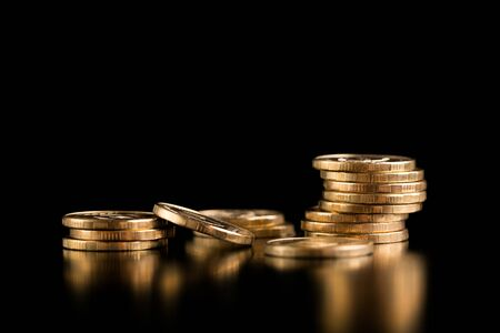 Scattered coins. Stack of gold coins on a black background. Stok Fotoğraf