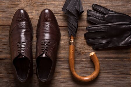 Men shoes, gloves and umbrella cane on a wooden background.