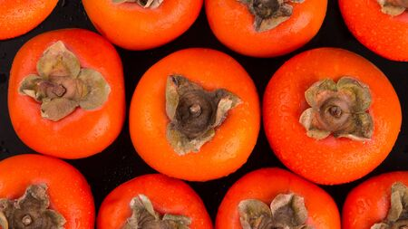 Persimmon background. Red ripe persimmon top view.