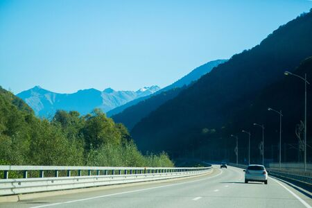Highway leading to the mountains. Caucasus Mountains and car route. Stok Fotoğraf