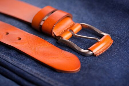 Leather belt in red. Fashionable orange-colored leather belt lies on blue jeans. Stok Fotoğraf