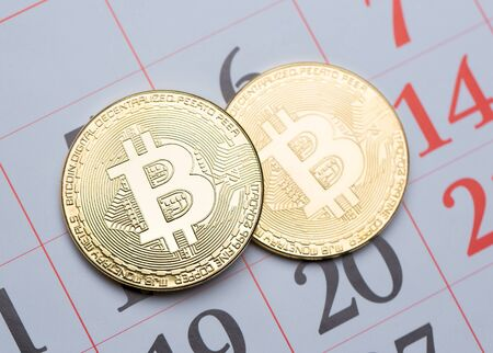 Gold Bitcoin coins and calendar. Cryptocurrency and paper calendar close-up. Stok Fotoğraf