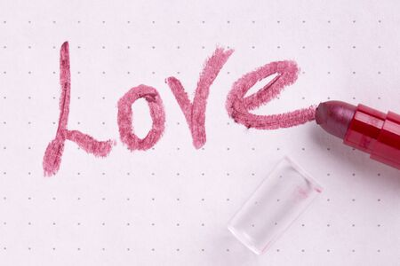 The word love written by lipstick on a sheet of paper.