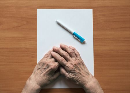 Pensioner writes in pen on paper. Senior citizen in front of a sheet of paper. Stok Fotoğraf - 128714482