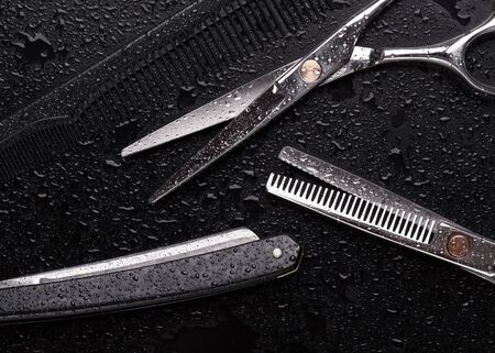 Scissors with comb and razor on a black background. Stok Fotoğraf - 128714487