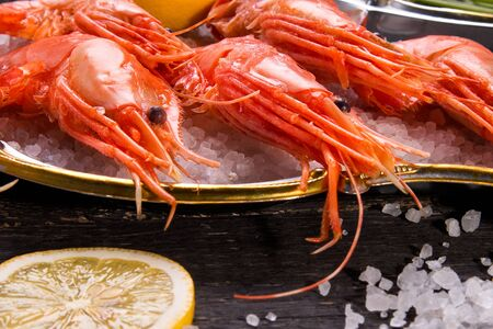 Shrimp, salt and lemon on a wooden background. Seafood.