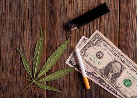 麻叶和美元顶视图上的木制背景。购买大麻。