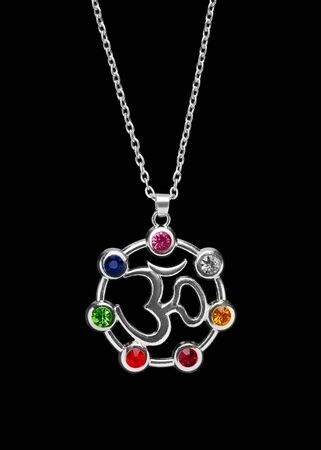 OM sign on a silver pendant surrounded by colored gemstones. OM on a black background. Banco de Imagens