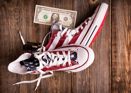 Sneakers lying on a wooden background. View from above. Youth culture and patriotism of America.