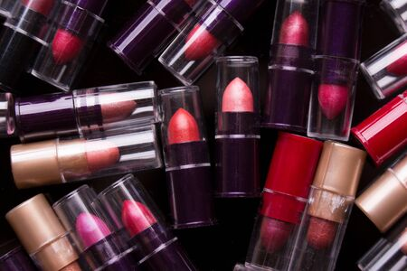 A lot of multi-colored tubes of lipstick. Pile of lipstick samplers closeup.