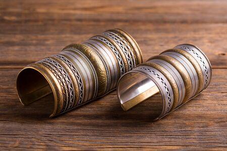 Breite schöne Bronzearmbänder mit Ornamenten. Schöne Damenarmbänder. Schmuck weibliche Hände.