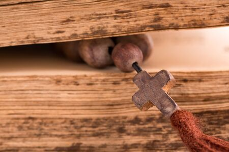 Church rosary with a cross and old sheets of an open bible.