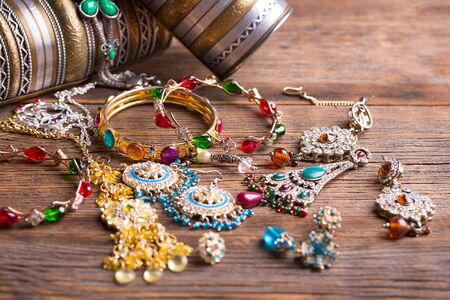 Beautiful jewelry close-up. Bracelets, pendants and earrings on the table. A collection of jewelry. Imagens