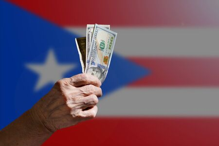 Elderly woman holding dollars in hand on a background of the Puerto rico flag. The concept of social problems of pensioners.