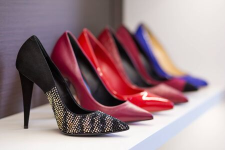 A collection of high-heeled shoes standing on a shelf in a store.