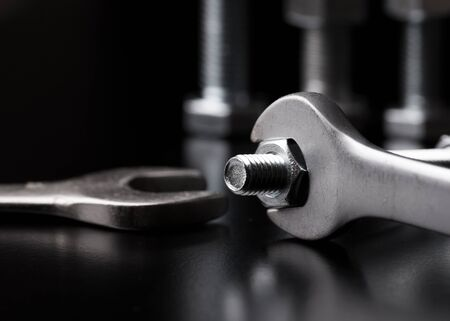The bolt is unscrewed with a wrench. Wrenches on a black background. Stock fotó