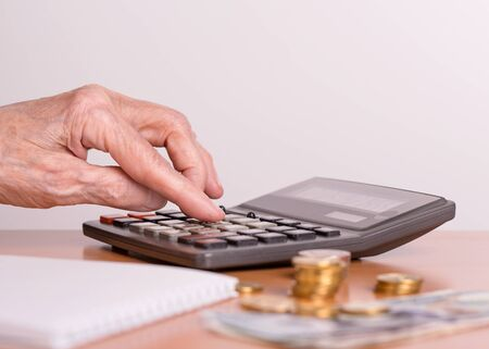 An elderly woman considers the amount of money on a calculator. The concept of the financial life of senior citizens. The budget of an elderly person.