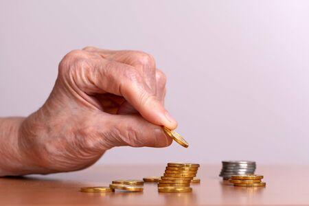 An elderly man counts gold coins. Senior citizen and money.