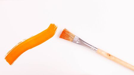Smear of orange paint applied with a brush on a white background.