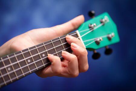 Vulture ukulele close-up. The girl plays a small ukulele.