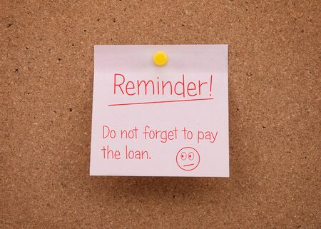A paper note with a reminder about the payment of the current loan. Credit Reminder.