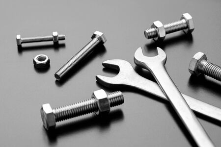 Wrenches and bolts on a dark background.