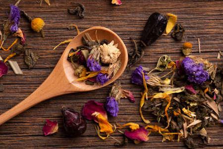 Healing tea made from dried flowers in a wooden spoon close-up. Archivio Fotografico