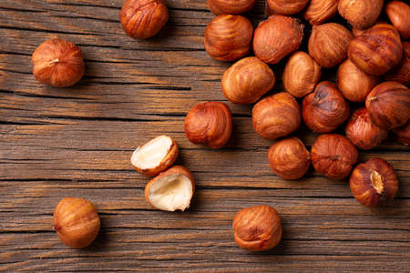 Peeled hazelnuts on a wooden background.