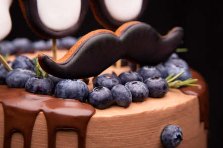 Chocolate cake with decorative elements and blueberries.