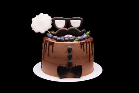 Big chocolate cake in masculine style on a black background. Archivio Fotografico - 158155411