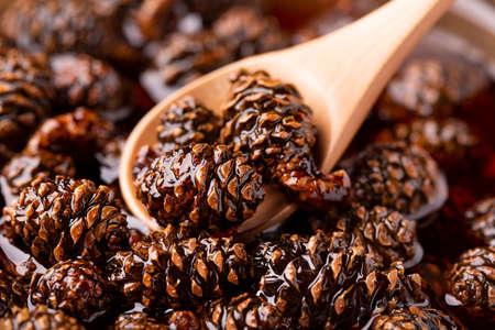 Small pine cones in sugar syrup. Archivio Fotografico - 158248863