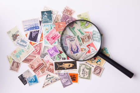 Postage stamps and magnifying glass. Archivio Fotografico