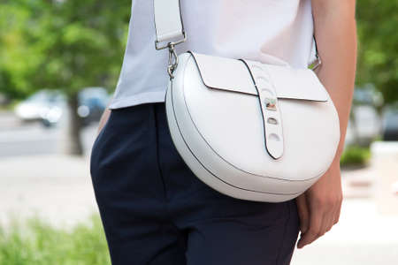 Girl with a white fashionable bag over her shoulder. Summer women's bag in white.