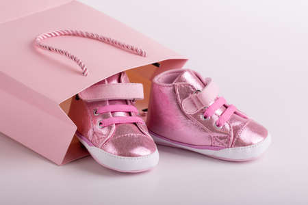 Pair of toddler sneakers sticking out of a paper bag.