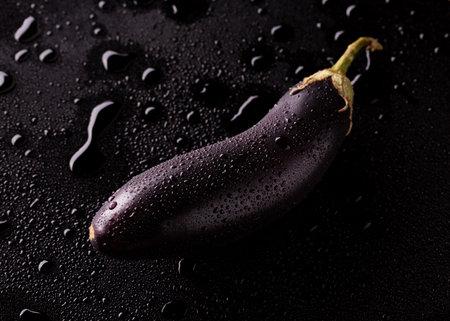 Eggplant in drops of water. Fresh eggplant. Фото со стока