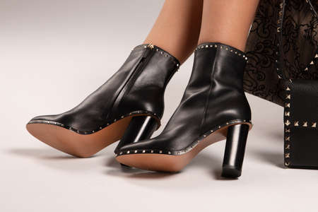 Girl in high-heeled shoes. Fashionable boots with high heels.