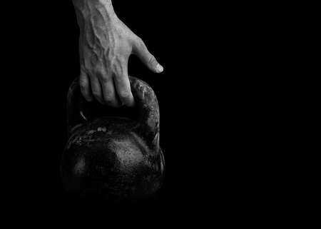 The athlete strong hand takes the kettlebell. Weight-lifting.