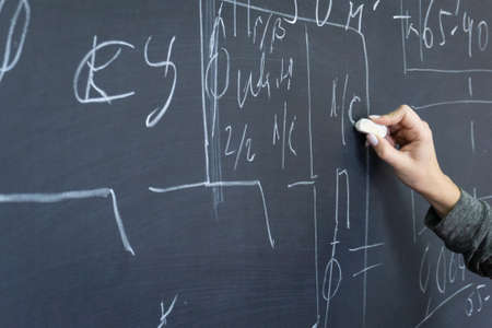 The girl writes on the blackboard with chalk. Education in an educational institution. Фото со стока