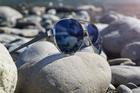 Aviator sunglasses on stones close-up.