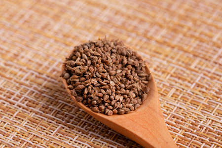 Dried anise seasoning. Anise seeds in a wooden spoon.