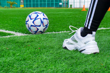 Soccer ball on green grass and foot of a soccer player in sneakers.