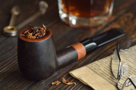 tamper: Stuffed with tobacco pipe lying on the table close to a newspaper