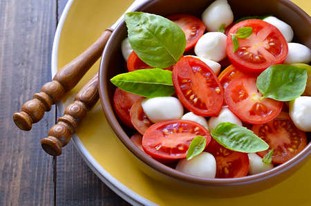Bowl of caprese salad. Mozzarella, basil leaves and summer tomatoes