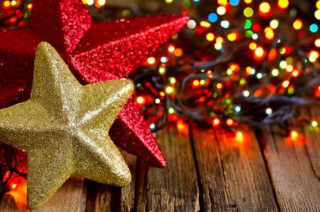Estrelas de brilho do Natal em um antigo fundo de madeira resistido em umas luzes guirlanda