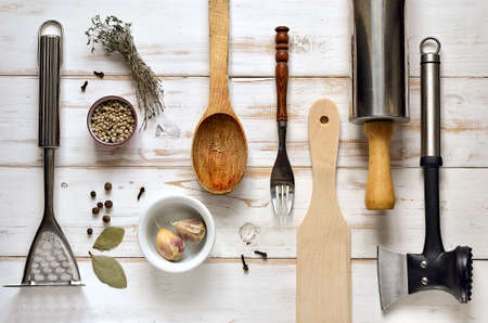 Kitchen utensils on a light rustic wooden background