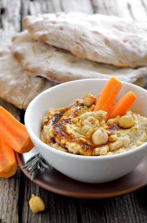 Recém cozida hummus bico servido com pita e as cenouras, decorado com azeite de oliva e páprica em pó