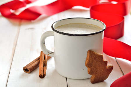 Christmas morning hot drink, maybe cocoa or coffee with milk,  with red holiday decoration photo
