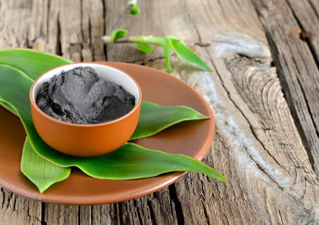 Cosmetic clay in a ceramic bowl decorated with fresh green leaves. Spa body and face treatment 스톡 콘텐츠